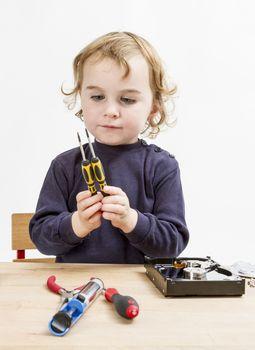 child choosing tool for repairing hard drive. Studio shot in gery background
