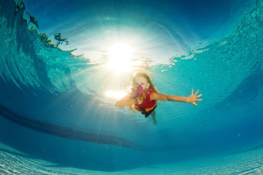 little girl underwater with bright flowers