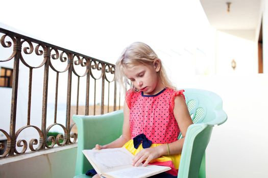 small girl reading book on the balcony