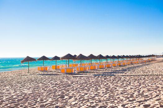 Empty beach with closed umbrellas on Portuguese coast