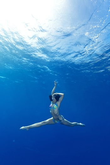 athletic girl making yoga in the sea