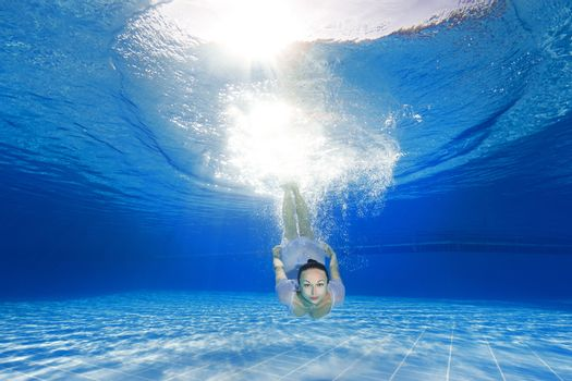 athletic girl diving in the swimming pool