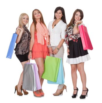 Four happy beautiful female shoppers carrying colorful shopping bags isolated on white