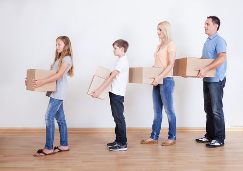 Parents And Two Children With Cardboard Boxes