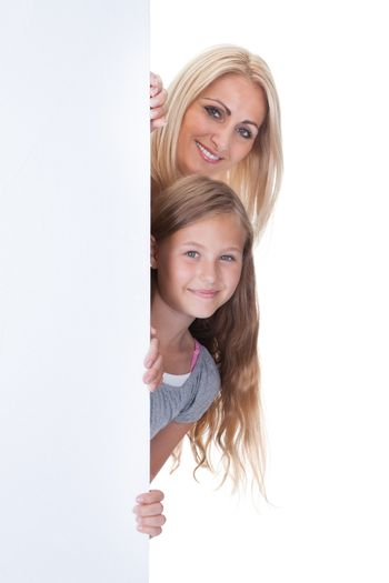 Portrait Of Mother and Girl Behind Blank Board