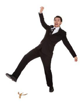 Businessman slipping on banana peel
