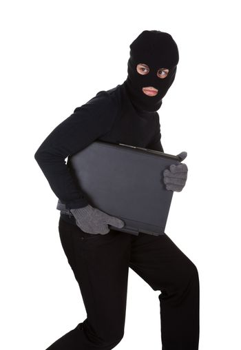 Thief stealing a laptop computer