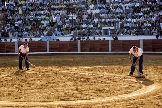 employees of the service from the plaza de toros de Pozoblanco smoothing the sand with a rake