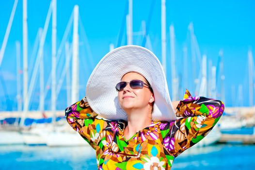 Portrait of a woman in panama hat on a background of yachts