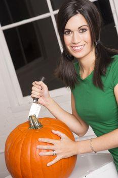 Excited Woman Cutting Carving Halloween Pumpkin Jack-O-Lantern