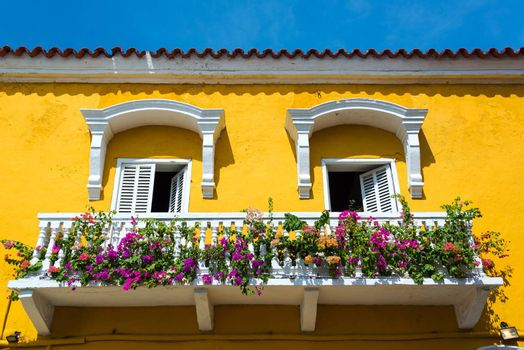 Historic yellow and white balcony in Cartagena, Colombia with colorful flowers