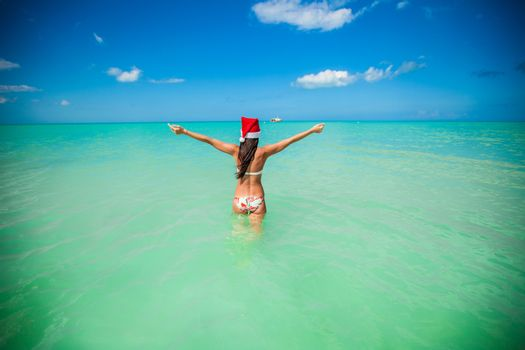 Back view of beautiful young woman in santa hat walking in the sea