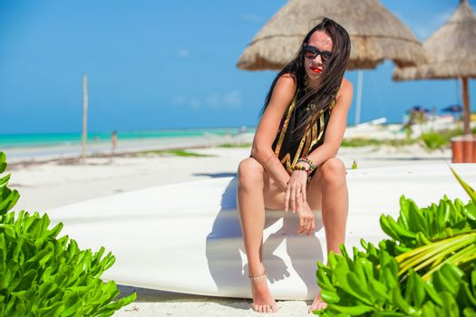 Young sexy woman sitting on a boat in white sandy beach