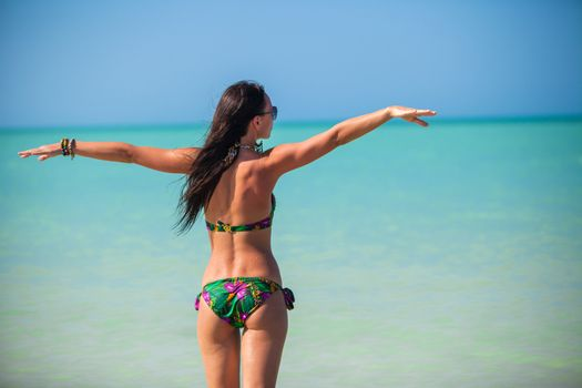 Young woman enjoying the holiday spread her hands on a white, tropical beach