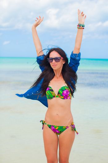 Young woman in swimsuit and denim jacket have fun on the beach