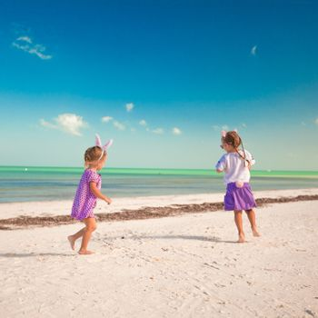 Two little cute girls in easter ears have fun on the exotic beach