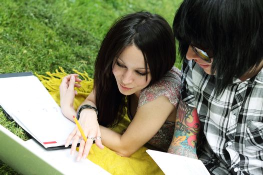 Couple of young students studying outdoors with laptop and books
