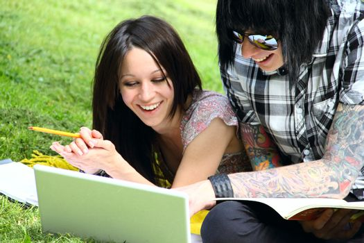 Couple of students studying outdoor with laptop
