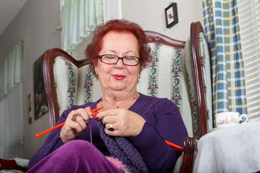 Senior woman relaxing while knitting, she sits on a fancy old classic style chair and pays attention to her crochet