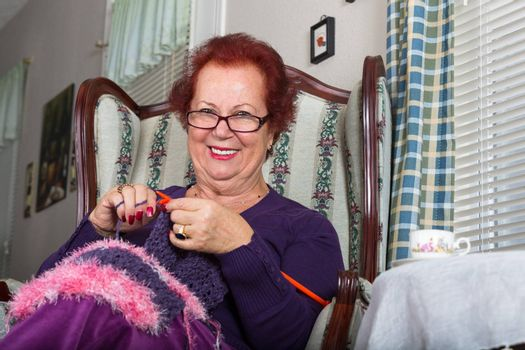 Red haired senior lady looking at you right abow her glasses while knitting her purple scarf