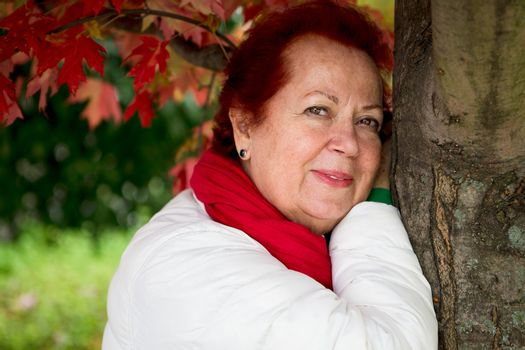 Red hair senior lady looking at you thoughtfully with her red scarf and white coat while leaning to the tree