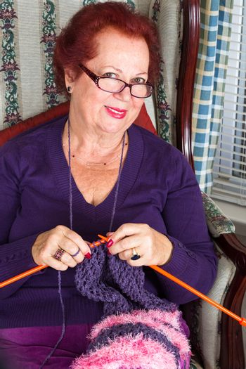 Red haired senior lady looking at you while knitting her purple scarf, she is wearing purple clothing perhaps purple is her favorite color