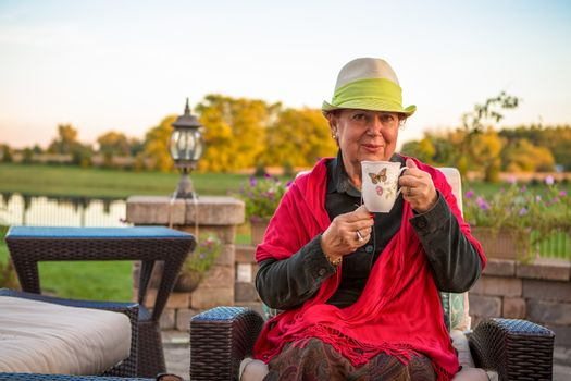 Senior woman with a straw green hat, sitting at the patio and showing her hot tea, perhaps she wants to stay warm