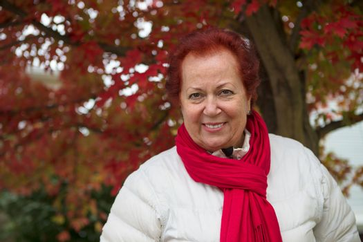 Red hair senior lady looking at you happily and trustfully with her red scarf and white coat under the tree with red falling leaves
