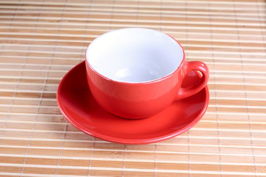 Empty red cup on the plate at the textured background