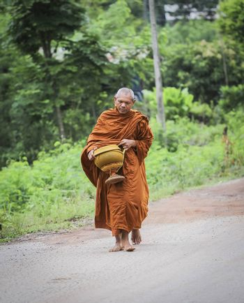 Every day very early in the morning, the monks walk the streets to beg give food offerings to a Buddhist monk