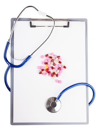 Blank sheet on clipboard with pills and stethoscope over white background