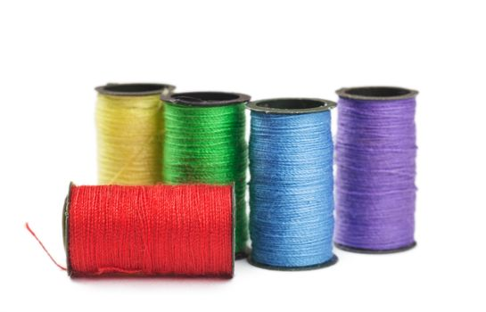 Five spools with green, red, yellow, violet and blue threads over white background