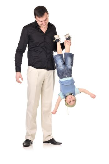 Man holds little boy upside down at white background