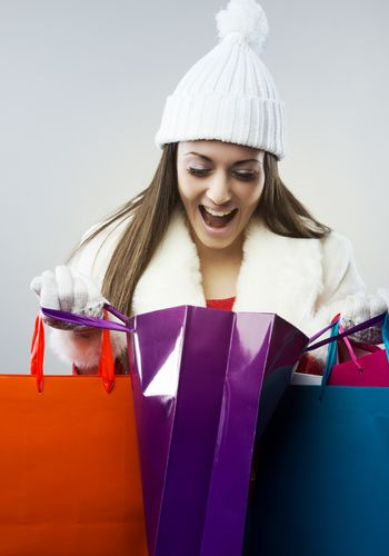 Young happy woman opening a shopping bag