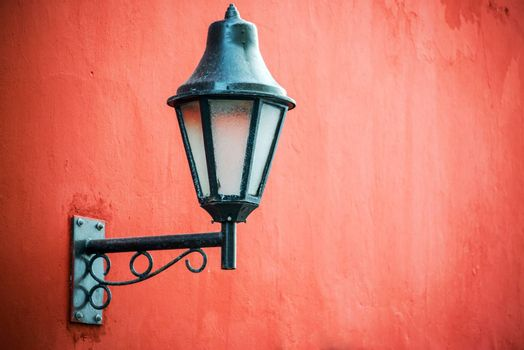 Historic colonial street light set against a vibrant red wall in Cartagena, Colombia