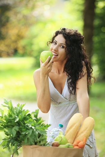 Cheerful young woman eating a green apple