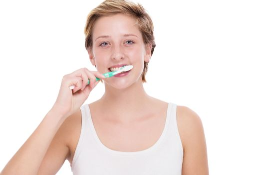 young blonde woman brushing her teeth with a toothbrush on white background