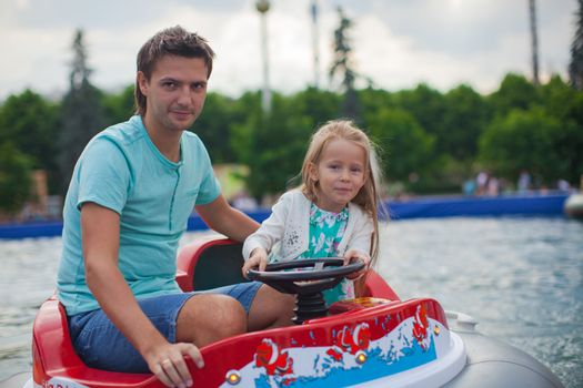 Young dad and his little girl riding on an airboat in the attraction