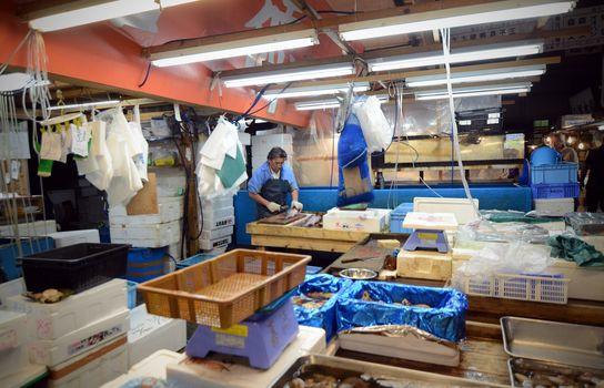 TOKYO- NOV 26: Worker processing fish at the Tsukiji Wholesale Fish market