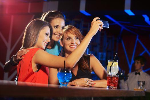 Three happy women at an nightclub party taking a self-portrait