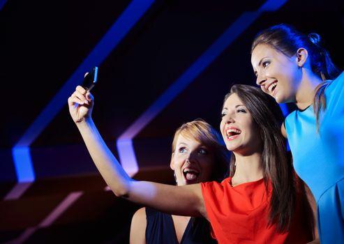 Friends in nightclub taking self-portrait with smartphone