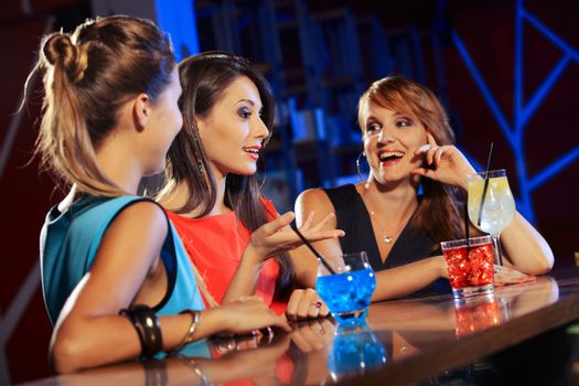 Three young women having a drink and talking in a night club