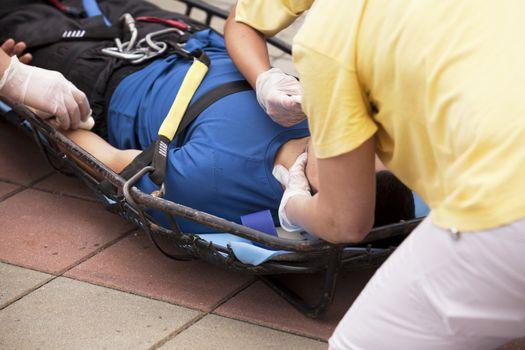 Paramedics putting a bandage on an injured hand