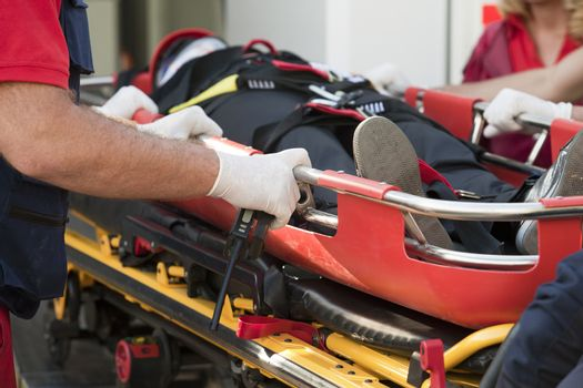 Paramedics rushing patient into an ambulance