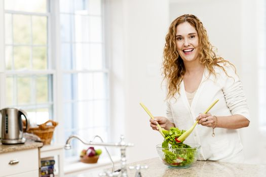 Smiling woman tossing salad in kitchen