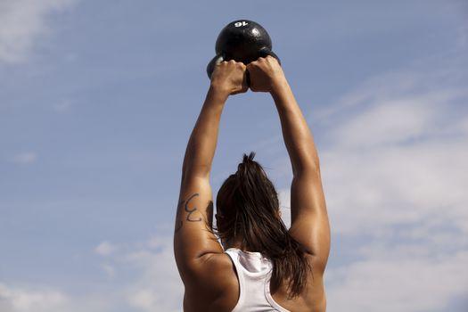 Woman doing kettlebell workout outside