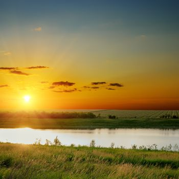 orange sunset over river with green sides