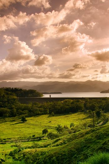 Scenic view of lake and green countryside under cloudscape on island of Costa Rica.