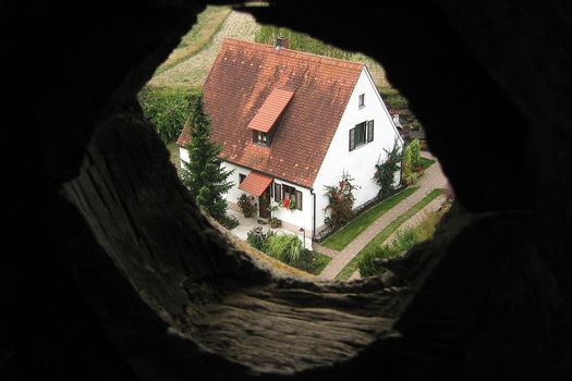 House viewed through hole in wall