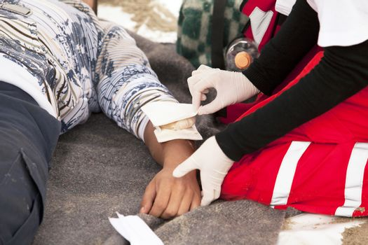 Paramedic applying bandage to arm of an accident victim
